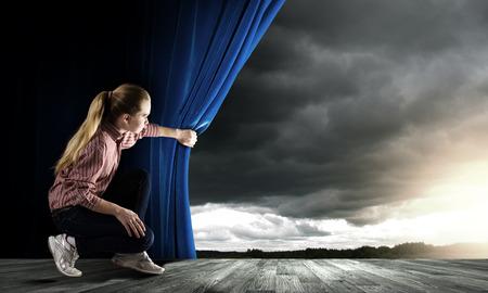 カジュアルで青いカーテンを開いて空を見て若い女性 写真素材