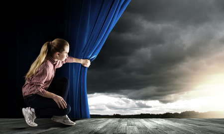 Young woman in casual opening blue curtain and looking at sky Stock Photo