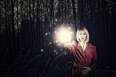 Young woman in red cloak with lantern lost in forest photo