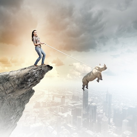 Young woman in casual and rhino flying in sky photo