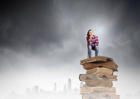 Young girl sitting on high pile of books photo