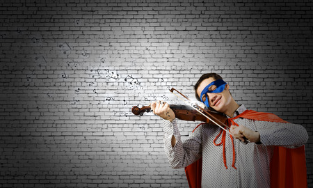 Young man in superhero costume playing violin photo