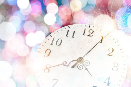 past midnight: Conceptual image of clock with bokeh lights and firework Stock Photo