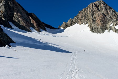 snows: Group of people walking among snows of New Zealand mountains