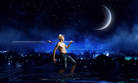 Boy of school age with fishing rod at night photo