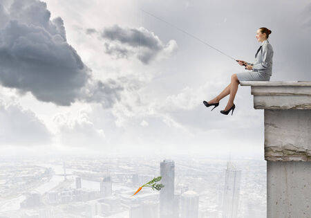 Young businesswoman sitting on top of building and fishing photo