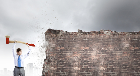 Young businessman breaking cement wall with axe photo