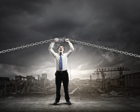 Young strong businessman tearing metal chain with hands photo
