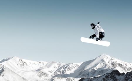 Snowboarder making high jump in clear blue sky 免版税图像