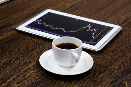 Tablet pc with graphs and cup of coffee on wooden table photo