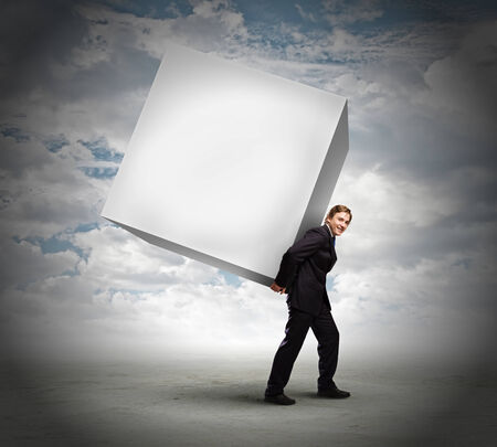 Young businessman carrying white big cube  Place for text photo