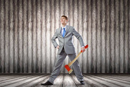 Young determined businessman with axe in hands photo