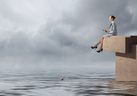 Young businesswoman sitting on top of building and fishing Stock Photo