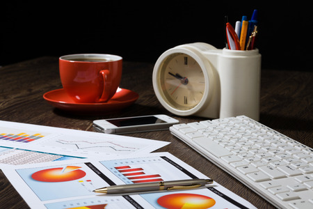 Workplace with keyboard cup of coffee and graphs photo