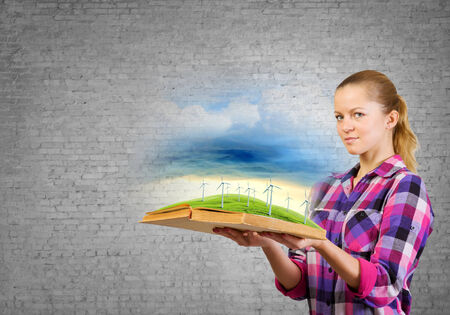 Young woman in casual holding opened book with windmills photo
