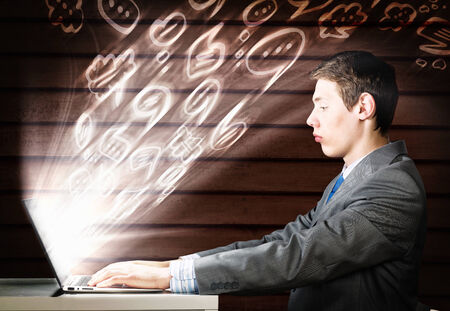 Young businessman looking shocked into laptop monitor photo