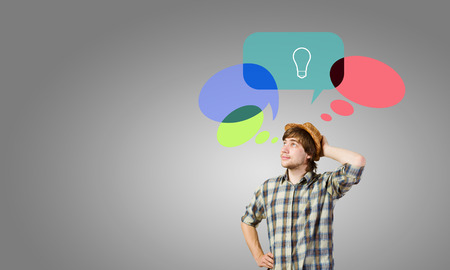 Young thoughtful man and colorful speech bubbles above photo