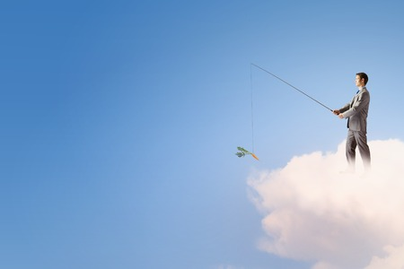 Young businessman standing on cloud high in sky and fishing