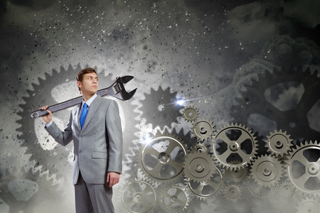 Young determined businessman with wrench on shoulder and cogwheels at background photo