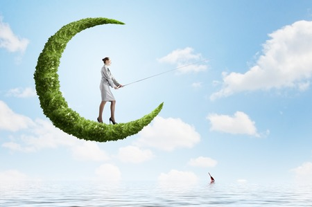 Businesswoman fishing with rod on green moon Stock Photo