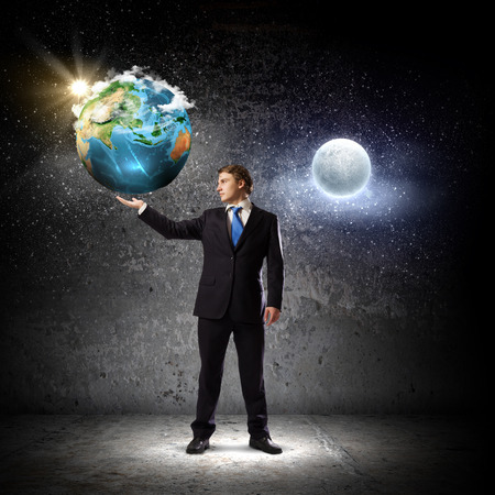 Young man in suit holding moon planet in palm  Elements of this image are furnished by NASA photo