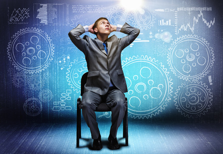 Young businessman sitting on chair and sketches at background photo