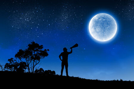 man in the moon: Silhouette of man screaming in trumpet at night Stock Photo