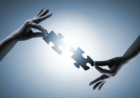 close up image: Close up image of hands connecting puzzle elements