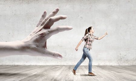 Young woman in casual escaping from big male hand Stock Photo