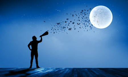 speaking trumpet: Silhouette of man screaming in trumpet at night Stock Photo