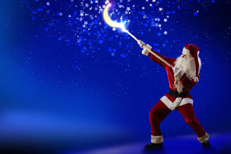 Santa Claus catching moon in night sky with rope photo