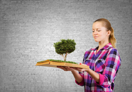 Young woman in casual holding opened book with green tree photo