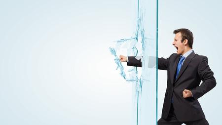 Young determined businessman breaking glass with karate punch Stock Photo
