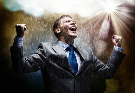 Vrolijke zakenman met handen omhoog vieren succes