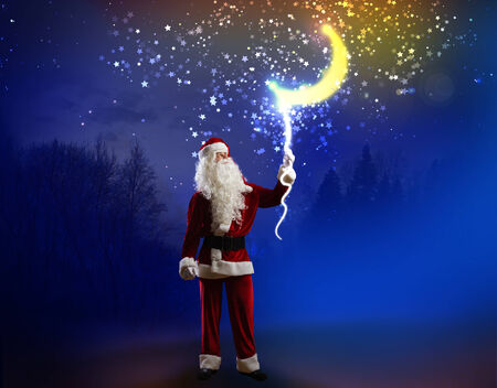 Santa Claus holding moon in night sky on rope photo