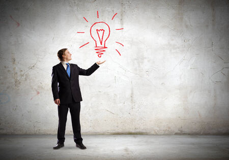 light brown hair: Businessman in suit holding light bulb in palm