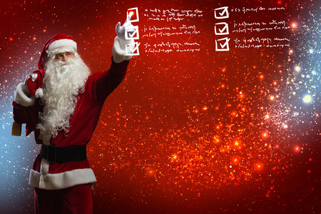 Santa Claus reading children letters with wishes photo