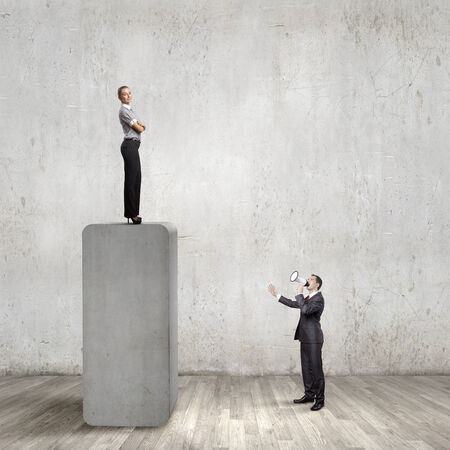 Businesswoman standing on top of bar and businessman screaming in megaphone photo
