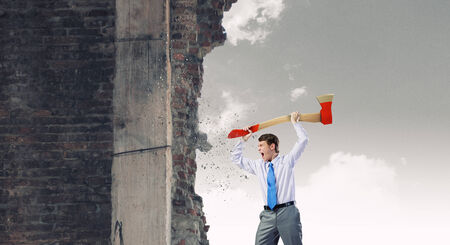 malefactor: Young determined businessman crashing wall with axe Stock Photo