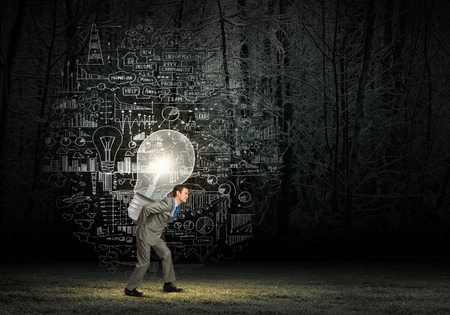 Tired businessman carrying light bulb on his back photo