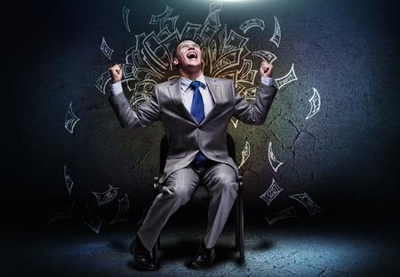 loteria: Hombre de negocios alegre sentado en silla bajo la lluvia de dinero Foto de archivo