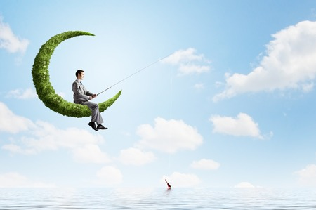 Young businessman standing on cloud high in sky and fishing photo