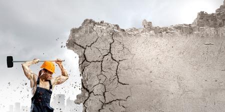 Sterke man in uniform breken muur met hamer