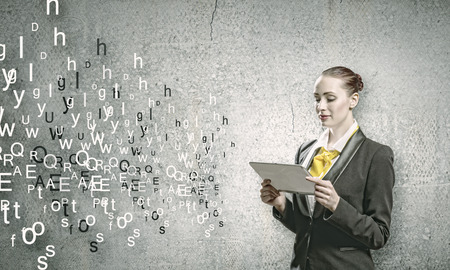 Young woman holding tablet pc in hands and letters flying around photo
