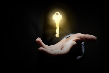 Close up image of business person holding shining key photo