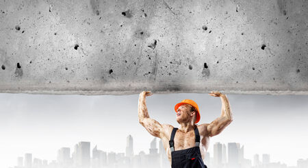Strong man in uniform lifting wall above head photo