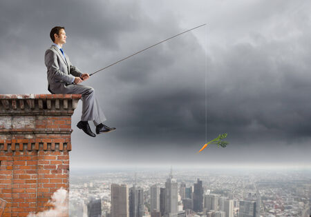 Young businessman sitting on top of building and fishing photo