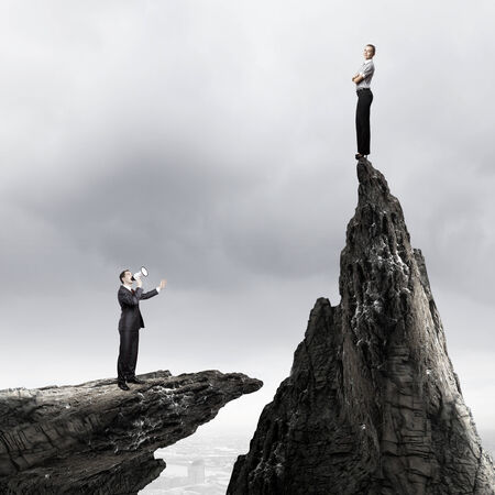 Businesswoman standing on top of rock and businessman screaming in megaphone photo