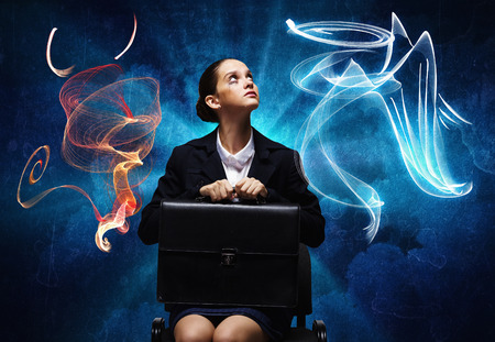 devil girl: Young troubled businesswoman making choice between good and bad Stock Photo