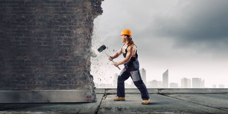 cement solution: Strong man in uniform breaking brick wall with hammer